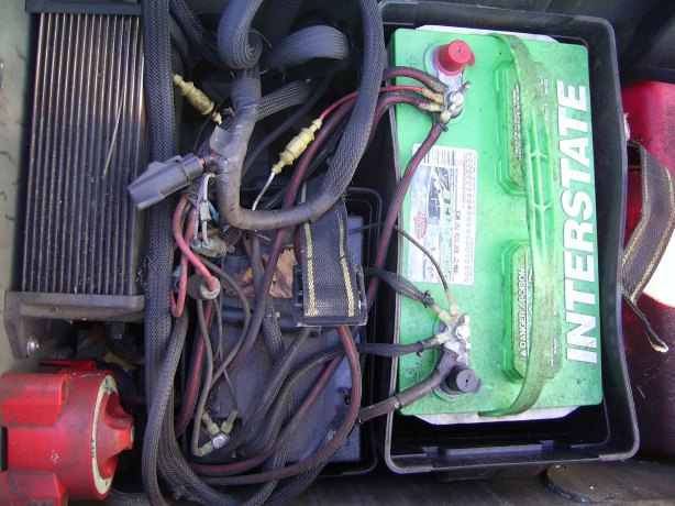 The battery/fuel compartment is very limited on space. Originally I had 2 wheelchair batteries as that served as power for my trolling motor, electronics, and various boat related items such as the bilge pump, the nav lights and engine. After the first set of batteries died, I shoehorned a full size trolling motor battery in. I swear by my Minnkota 2 bank charger. It's performed better than I ever could have imagined and had extended the life cycle of my batteries by a large amount. As you can see, the wiring harness is in good shape, just a hair messy, and to my great misfortune, unlabeled, so I will be spending some time sorting out the wiring.